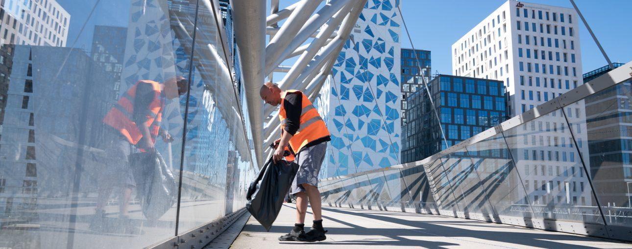 Mann i oransje vest fra Kirkens Bymisjon plukker søppel.
