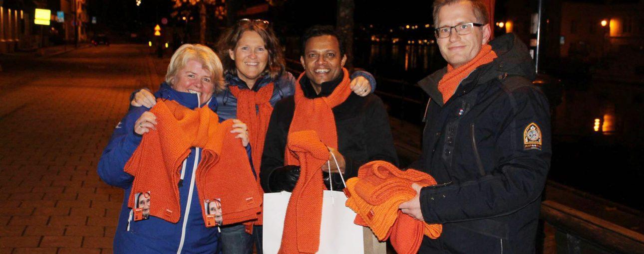 Samarbeidspartnere Arendal ute og deler ut oransje skjerf for Kirkens Bymisjon. Bilde