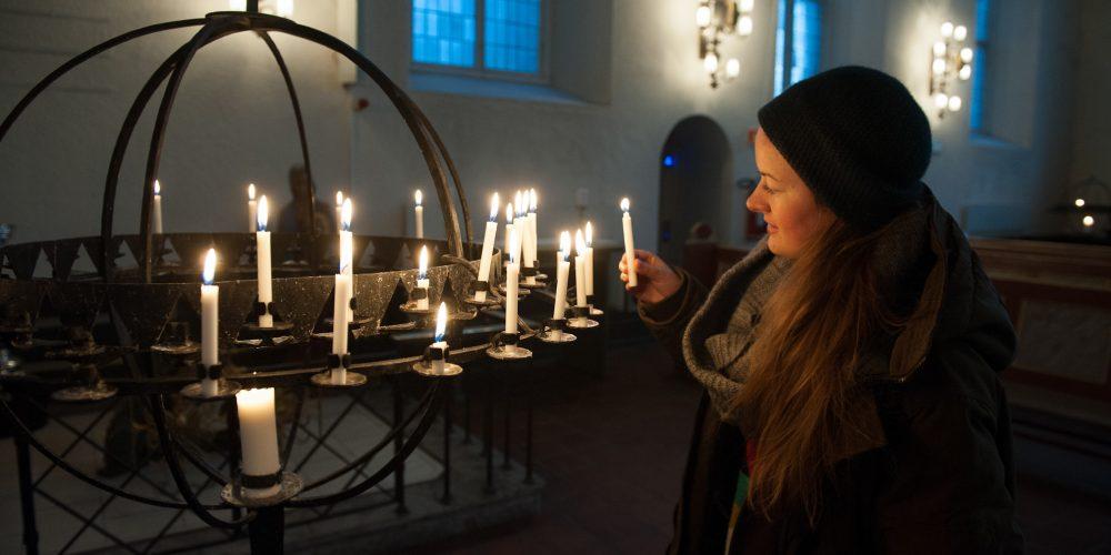 Bilde av en ung jente som tenner lys på lysgloben i domkirken på kveldstid. Bilde