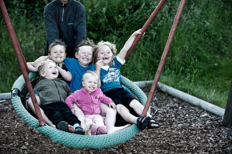 Glade barn jubler og sitter i en stor huske.Glade barn jubler og sitter i en stor huske.