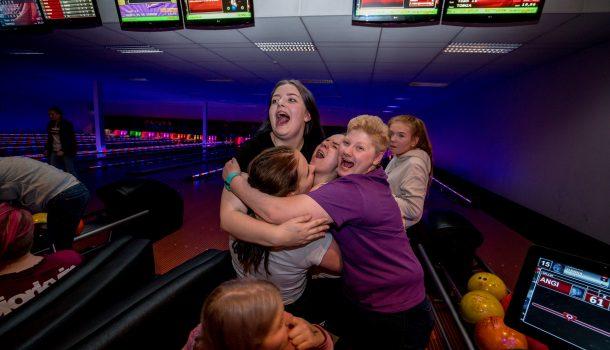 Bildet viser fire unge mennesker som holder rundt hverandre i en klynge. De står foran en bowlingbane og jubler.