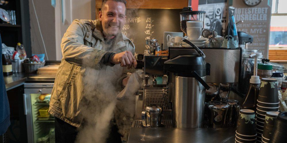 Tony, frivillig på cafeen Møtestedet i Halden, smiler ved kaffemaskinen. Han får ofte høre at han serverer Haldens beste kaffe, på kafeen som ligger på togstasjonen og er drevet av Kirkens Bymisjon.