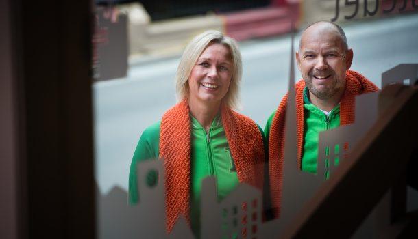 Bilde av to grønnkledde ansatte fra Kiwi med oransje skjerf rundt halsen. Bilde