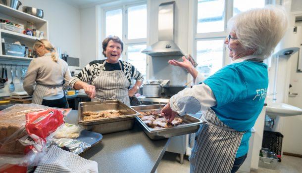 Bilde av to damer som står og ler og smiler på et kjøkken mens de lager mat.