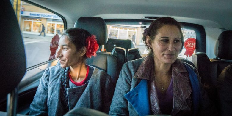 Bilde av to kvinner som sitter i baksetet på en taxi, pyntede og ser glade ut.