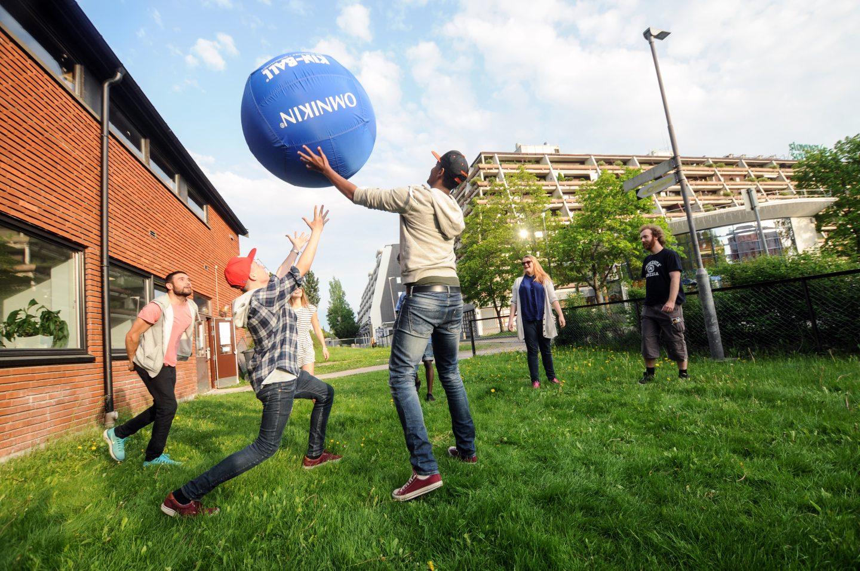 Unge frivillige på Stivner kaster ball på plenen.
