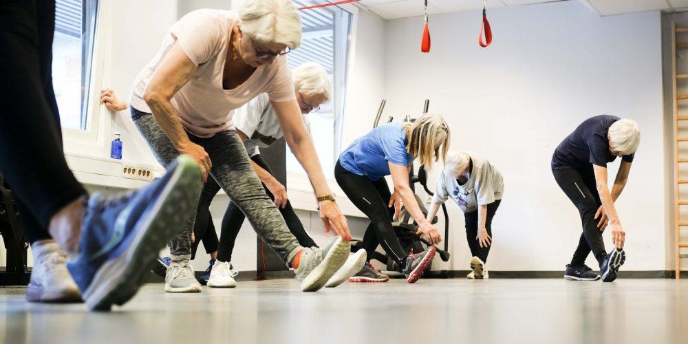 Eldre mennesker trener. De bøyer seg ned for å ta på skotuppen.