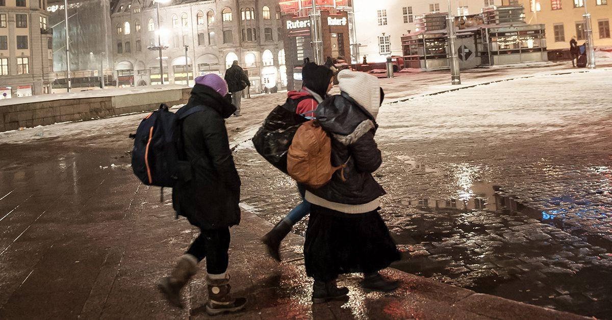 Tre kvinner går over jernbanetorget på vinteren.