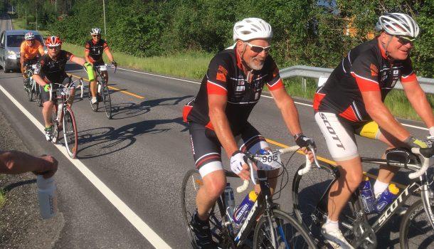 Frode Forsdahl og Ulf Axelsen på sykkelsetet på en landevei, med hvite hjelper og Kirkens Bymisjon-sykkeldrakt, tre syklister og en følgebil bak seg.