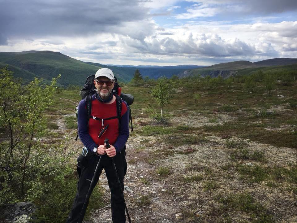 Bilde av Lars Kristian Hemstad med utsikt utover nydelig natur bak seg.