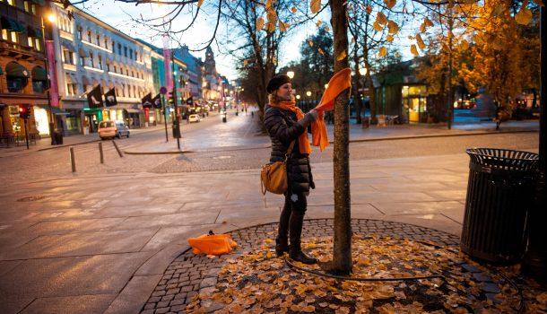 Dame på Karl Johan henger oransje skjerf på et tre.
